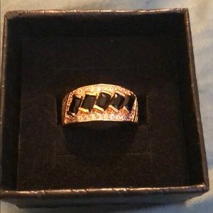 Gold tone ring with black stones.